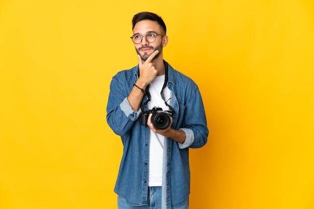 Jong fotograafmeisje dat op gele achtergrond wordt geïsoleerd die twijfels heeft