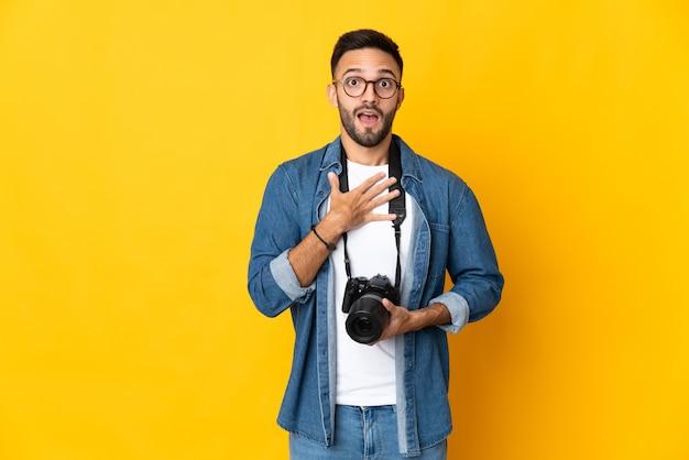 Jong fotograafmeisje dat op gele achtergrond wordt geïsoleerd die verrast en geschokt terwijl naar rechts kijkt