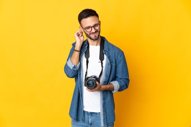 Jong fotograafmeisje dat op gele gefrustreerde achtergrond wordt geïsoleerd en oren bedekt