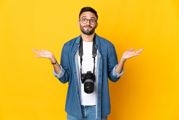 Jong fotograafmeisje dat op gele muur wordt geïsoleerd die twijfels heeft terwijl het opheffen van handen