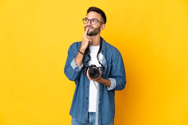 Jong fotograafmeisje dat op gele muur wordt geïsoleerd die twijfels heeft tijdens het kijken