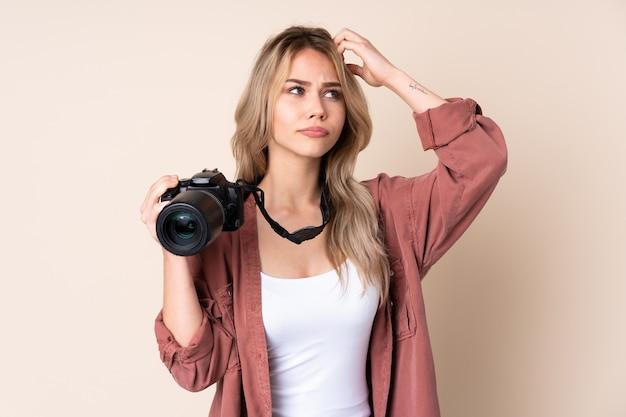Jong fotograafmeisje over geïsoleerd die twijfels hebben terwijl het hoofd krabben