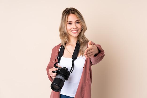 Jong fotograafmeisje over geïsoleerd handen schudden voor het sluiten van een goede overeenkomst
