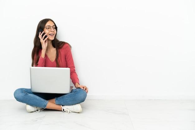 Jong frans meisje dat op de grond zit met haar laptop en een gesprek voert met de mobiele telefoon