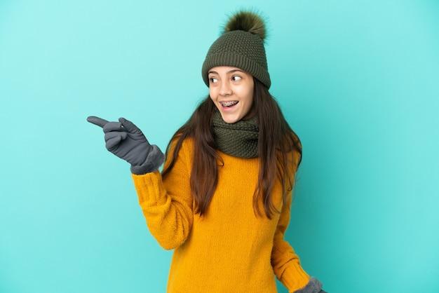 Jong frans meisje geïsoleerd op blauwe achtergrond met wintermuts van plan om de oplossing te realiseren terwijl ze een vinger optilt