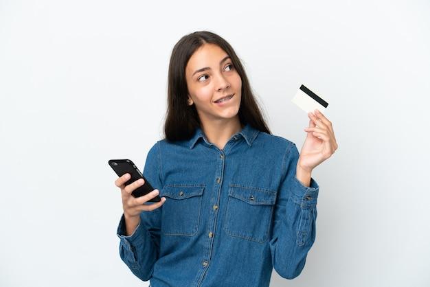 Jong frans meisje geïsoleerd op een witte achtergrond te kopen met de mobiele telefoon met een creditcard tijdens het denken