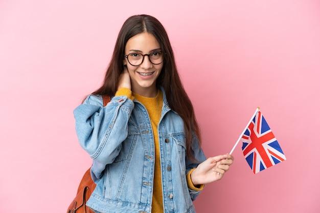 Jong frans meisje met een vlag van het verenigd koninkrijk geïsoleerd lachend