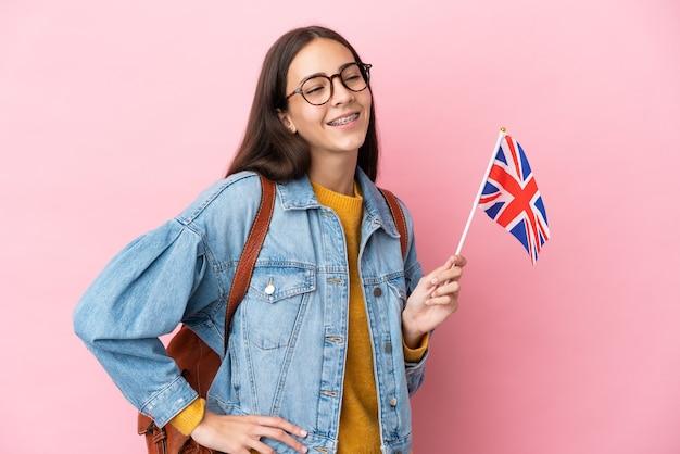 Jong frans meisje met een vlag van het verenigd koninkrijk geïsoleerd op roze achtergrond poseren met armen op heup en lachend