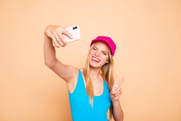 Jong funky meisje dat v-sign tong toont die zelfbeeld met slimme telefoon maakt