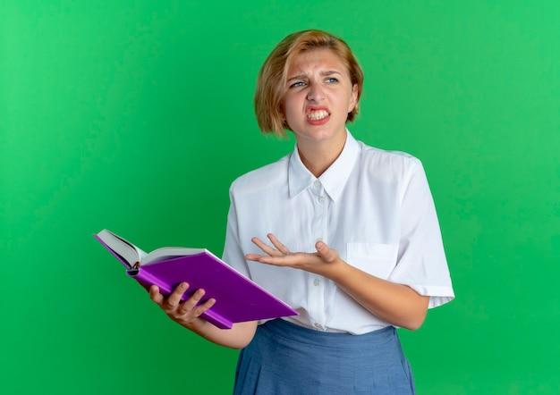 Jong geërgerd blond russisch meisje houdt en wijst op boek dat op groene achtergrond met exemplaarruimte wordt geïsoleerd
