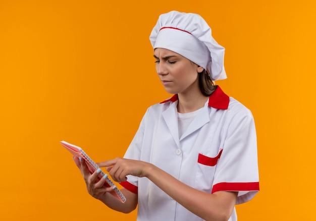 Jong geïrriteerd kaukasisch kokmeisje in eenvormige chef-kok houdt en bekijkt notitieboekje dat op oranje achtergrond met exemplaarruimte wordt geïsoleerd
