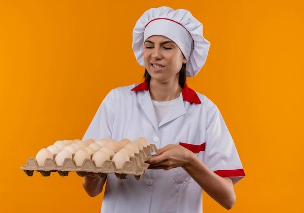 Jong geïrriteerd kaukasisch kokmeisje in eenvormige chef-kok houdt en bekijkt partij eieren die op oranje achtergrond met exemplaarruimte worden geïsoleerd