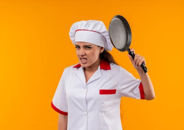 Jong geïrriteerd kaukasisch kokmeisje in eenvormige chef-kok houdt koekenpan die op oranje achtergrond met exemplaarruimte wordt geïsoleerd