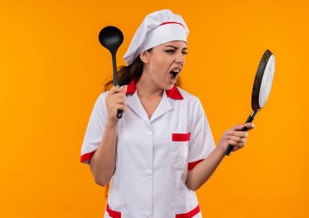 Jong geïrriteerd kaukasisch kokmeisje in eenvormige chef-kok houdt koekenpan en lepel die op oranje achtergrond met exemplaarruimte wordt geïsoleerd
