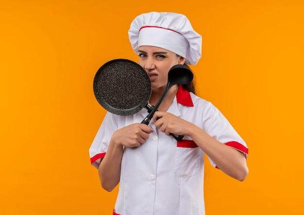 Jong geïrriteerd kaukasisch kokmeisje in eenvormige chef-kok kruist koekenpan en pollepel die op oranje achtergrond met exemplaarruimte wordt geïsoleerd