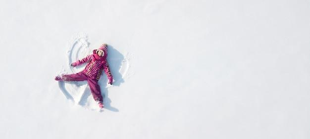 Jong geitje dat een sneeuwengel maakt. uitzicht van boven