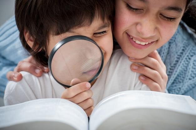 Jong geitje dat en het boek met meer magnifier leest onderzoekt