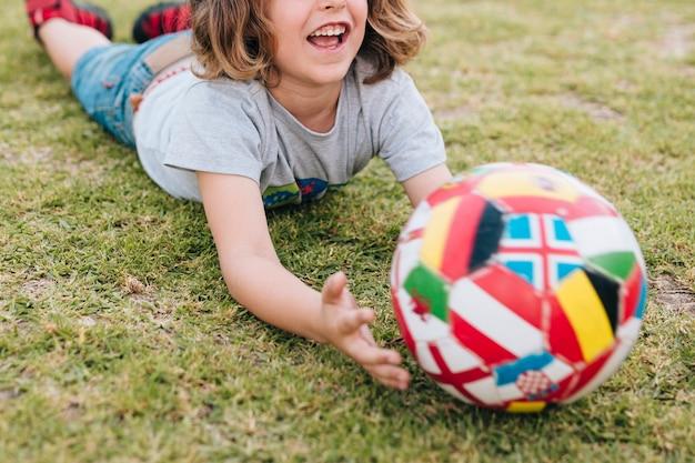 Jong geitje dat in gras ligt en met bal speelt