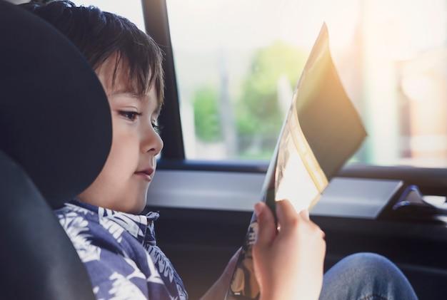 Jong geitje dat op autostoel situeert en een boek leest, kleine jongenszitting in de auto in kinderveiligheidszetel, portret van peuter die himserf op een wegreis onderhouden. concept veiligheid taveling door auto met kinderen