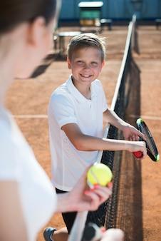 Jong geitje dat vrouw op het tennisgebied bekijkt