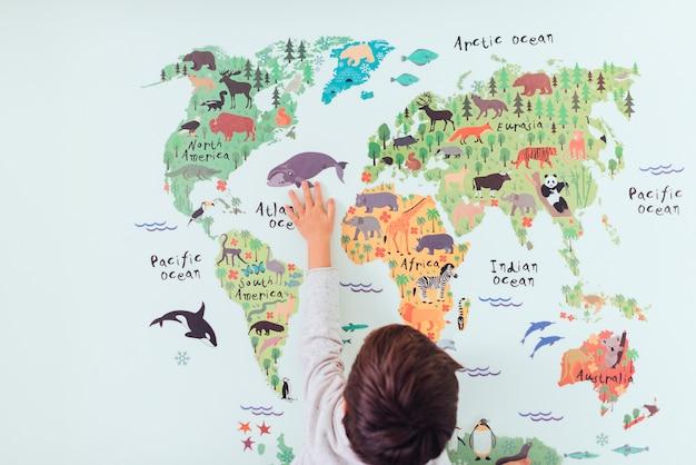 Jong geitje die wereldkaart bekijken