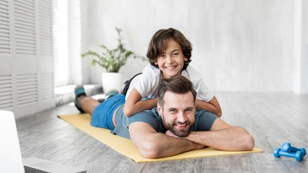 Jong geitje en zijn vader die sport thuis doen