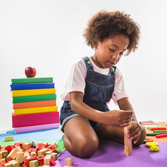 Jong geitje het spelen met kubussen op spelmat in studio