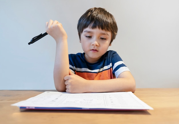 Jong geitje in zelfisolatie die zijn wiskundehuiswerk doen terwijl school weg, kind die wiskunde thuis leren tijdens covid lock down, huisonderwijs.