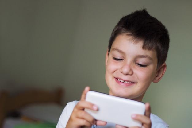 Jong geitje met behulp van een mobiele smartphone en lachend