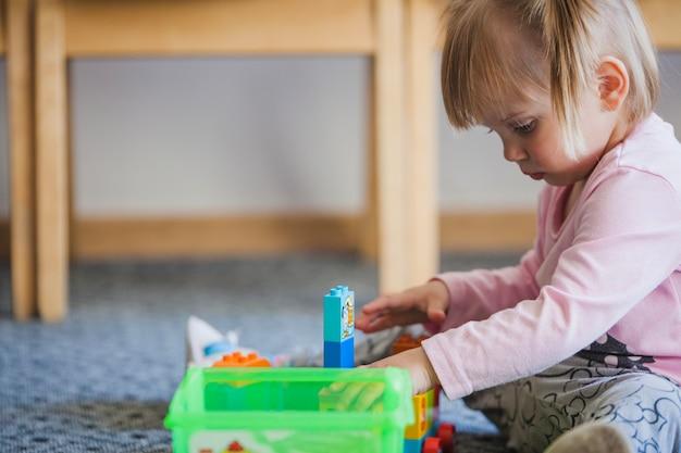 Jong geitje met speeltoestellen in de kleuterschool