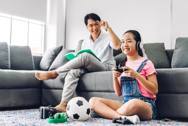 Jong geitje weinig aziatisch meisje die pret hebben die van het videospel van de spelconsole met vader genieten terwijl thuis het zitten op laag
