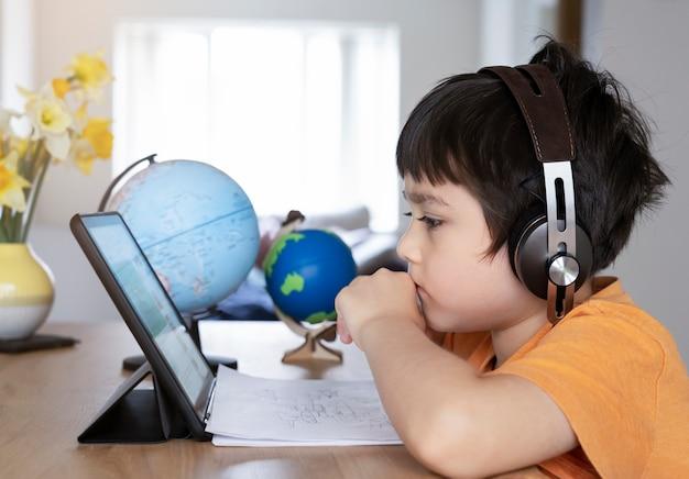 Jong geitje zelfisolatie die tablet voor zijn huiswerk gebruiken, kind die gebruikend digitale tablet die informatie zoeken op internet doen