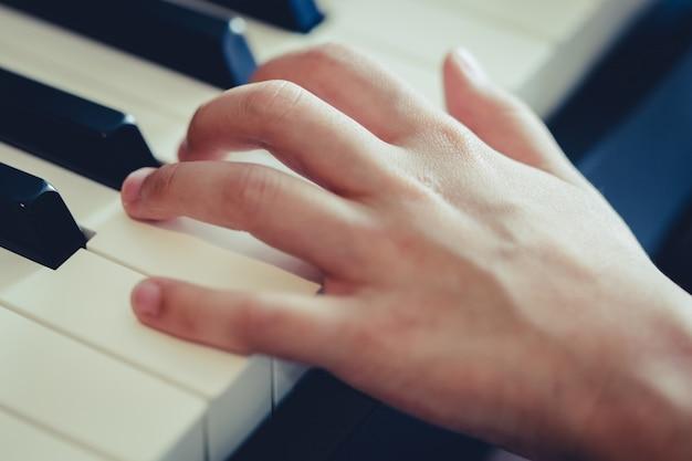 Jong geitjehand die op pianotoets drukken voor muziekconcept