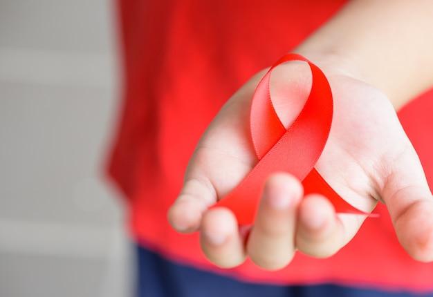 Jong geitjehanden die rood de voorlichtingslint van aids houden. aids-bewustwordingscampagne