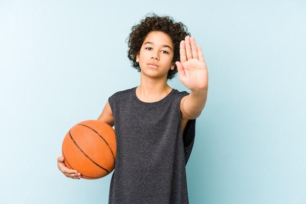 Jong geitjejongen die basketbal spelen dat op blauwe muur wordt geïsoleerd die zich met uitgestrekte hand bevindt die stopbord toont, dat u verhindert.