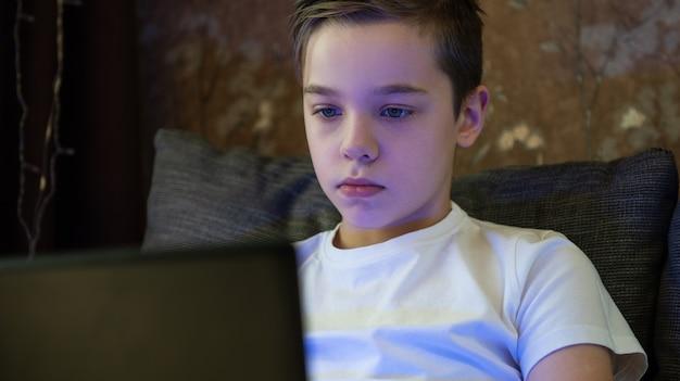 Jong geitjejongen of tiener die thuis op laptop voor school leren