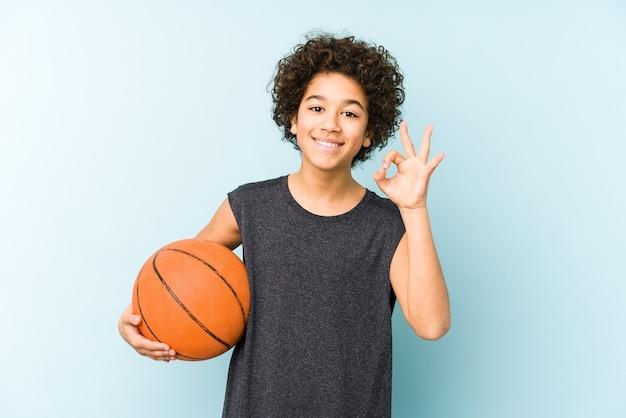 Jong geitjejongen speelbasketbal dat op blauwe muur wordt geïsoleerd vrolijk en zelfverzekerd tonend ok gebaar.