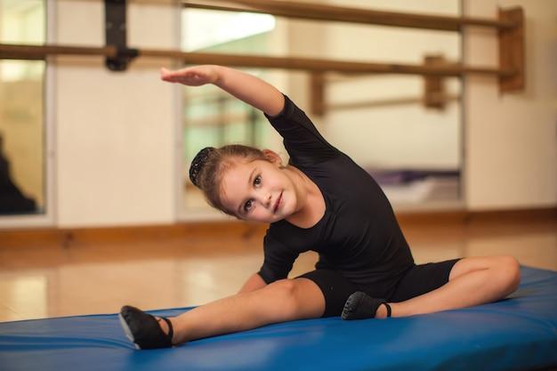 Jong geitjemeisje bij gymnastiekles die oefeningen doet. kinderen en sport concept