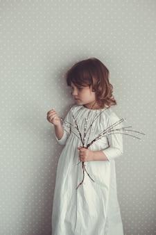 Jong geitjemeisje in nachtjapon retro met takjes wilg