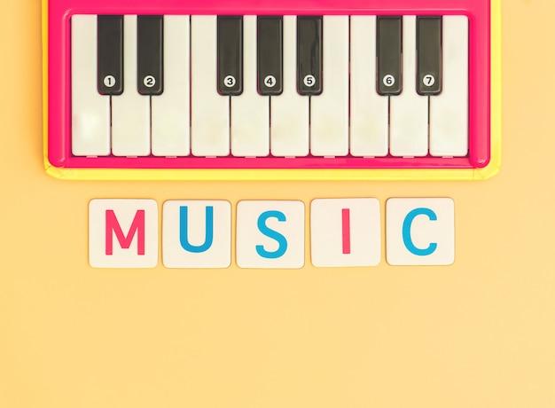 Jong geitjemuziek met stuk speelgoed toetsenbord op oranje achtergrond