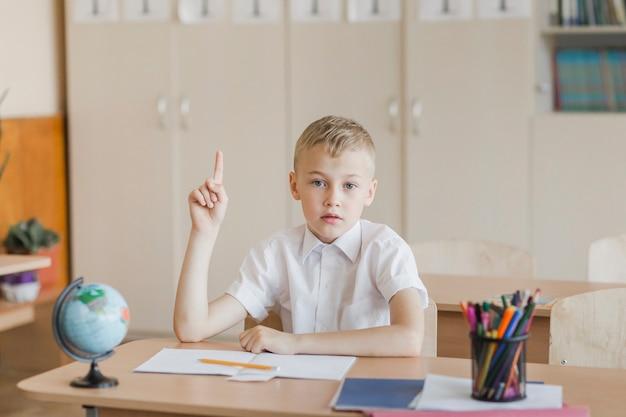 Jong geitjezitting bij bureau in klaslokaal dat hand opheft