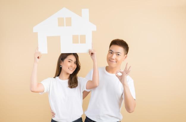 Jong gelukkig aziatisch paar dat de symbolen van huis voorstelt