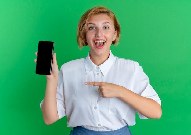 Jong gelukkig blond russisch meisje houdt en wijst op de telefoon