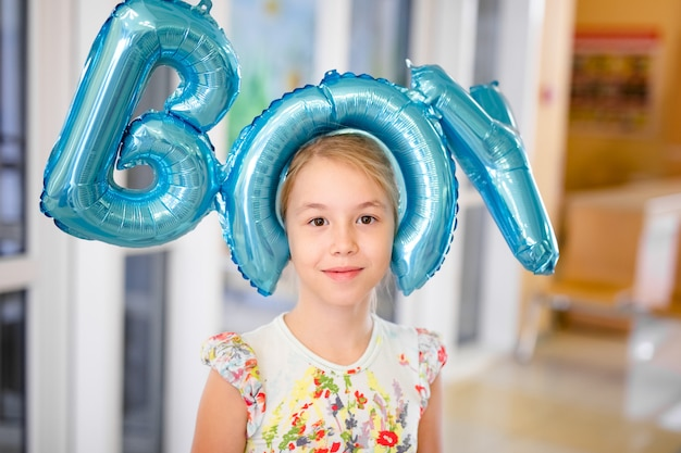 Jong gelukkig blondemeisje die met baloons dicht omhoog glimlachen