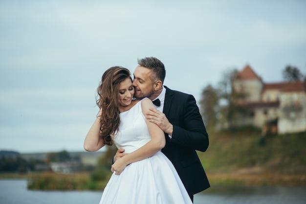 Jong gelukkig bruidspaar knuffelen en kussen op de achtergrond van het kasteel en het meer in de herfst