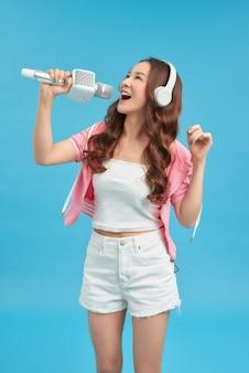 Jong gelukkig en mooi aziatisch meisje zingt karaokelied opgewonden, vrolijk emulerend popmuziekster
