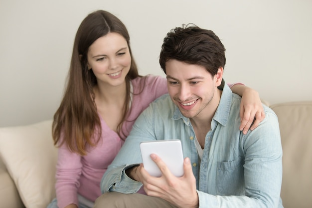 Jong gelukkig glimlachend paar die tablet, videovraag, online winkel gebruiken