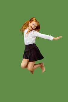 Jong gelukkig kaukasisch tienermeisje dat in de lucht springt, dat op groene studioachtergrond wordt geïsoleerd. mooi vrouwelijk portret van halve lengte. menselijke emoties, gezichtsuitdrukking concept.