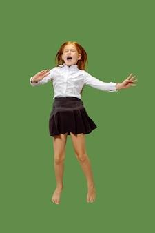 Jong gelukkig kaukasisch tienermeisje dat in de lucht springt, dat op groene studioachtergrond wordt geïsoleerd. mooi vrouwelijk portret van halve lengte.