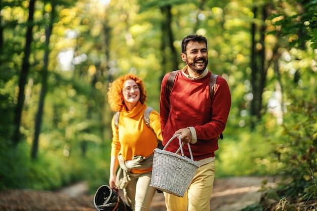 Jong gelukkig lachend paar verliefd hand in hand en wandelen in de natuur. herfst tijd.